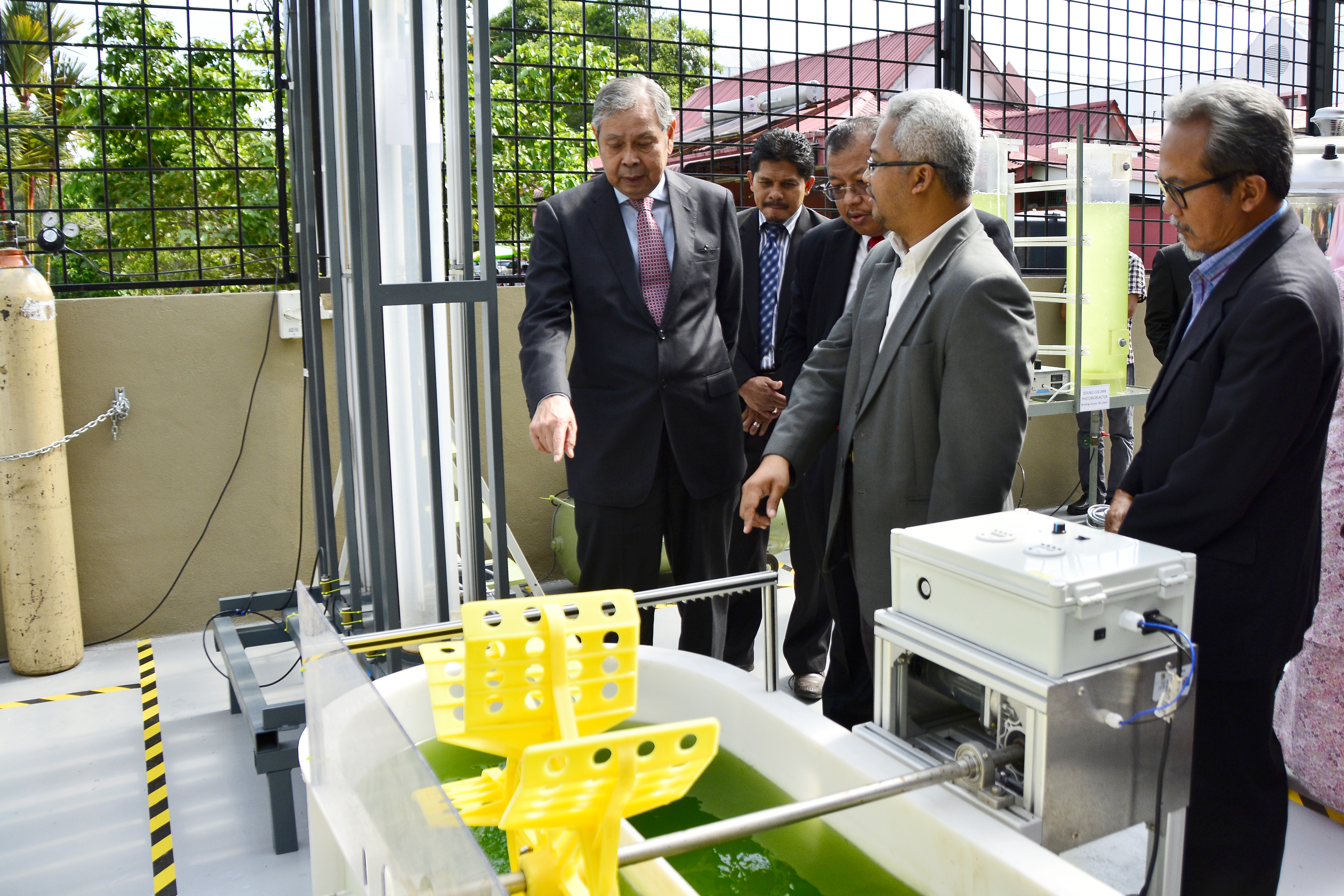 YSD Governing Council Member Tan Sri Dato' Seri Dr Wan Mohd Zahid Mohd Noordin (left) inspects algae growth at UKM's carbon capture lab.
